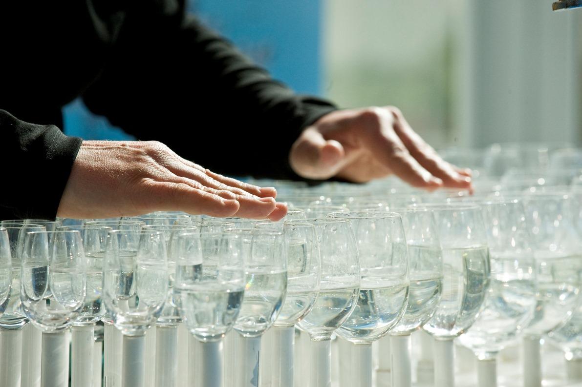 Künstler erzeugt auf mit Wasser gefüllten Gläsern Musik